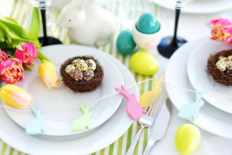 tavola apparecchiata pasqua nidi uova tulipani rosa giallo uova colorate conigli posate piatti