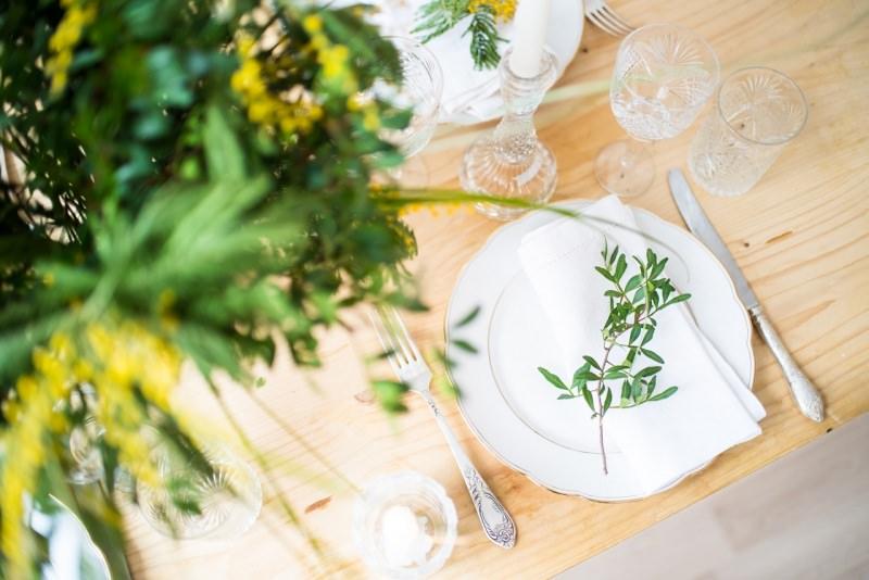 segnaposto ramo ulivo su tovagliolo bicchieri calici cristallo fiori gialli mimosa tavola festa pasqua domenica palme