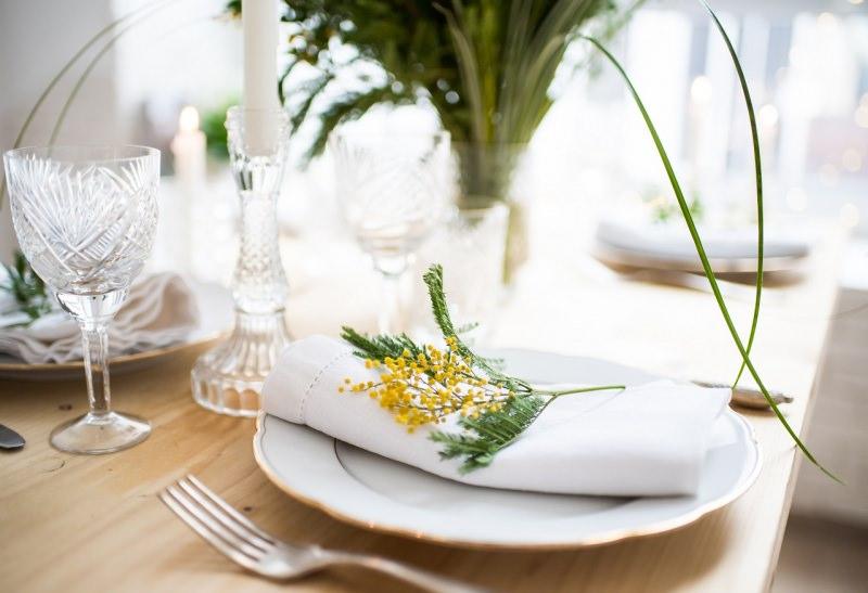 segnaposto ramo mimosa fiori gialli su tovagliolo tavola apparecchiata festa pasqua