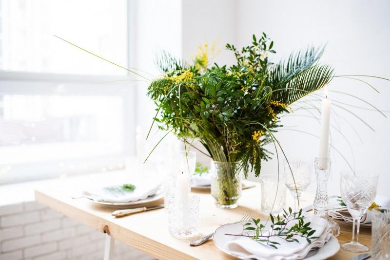 tavola apparecchiata domenica Palme Pasqua centrotavola vaso cristallo foglie verdi fiori di mimosa segnaposto ramo ulivo festa