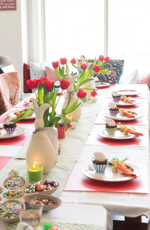 tavola apparecchiata festa di Pasqua centrotavola con bouquet di tulipani rossi bicchieri candele ovetti di cioccolato confetti conigli ceramica bianca