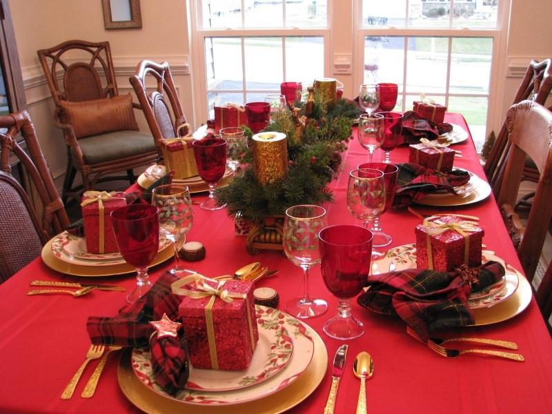 Come apparecchiare la tavola di Natale tovaglia rossa tovaglioli tartan tessuto scozzese rosso nero pacco regalo segnaposto centrotavola candele foglie abete tealights