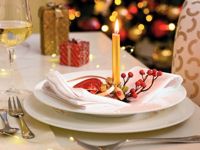 Come apparecchiare la tavola di Natale pacchi regalo tovaglia bianca calice vino bianco segnaposto candela fiamma accesa luci albero palla