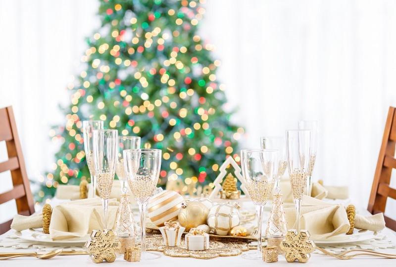 tradizioni di natale a tavola apparecchiata a festa bianco oro calici albero natalizio