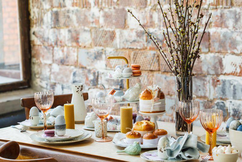tavola apparecchiata di pasqua uova segnaposto candele torta pane ceramiche calici