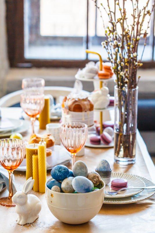 tavola apparecchiata festa di pasqua uova colorate calici candele conigli