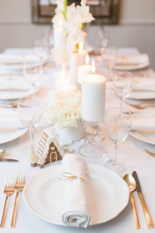 Come apparecchiare la tavola di Natale tovaglia bianca candele fiori piatto tovaglioloposate casetta pan di zenzero