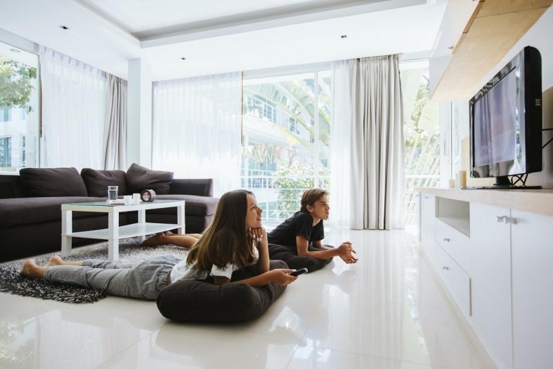 Teenagers ragazzo e ragazza guardano tv in soggiorno in casa divano