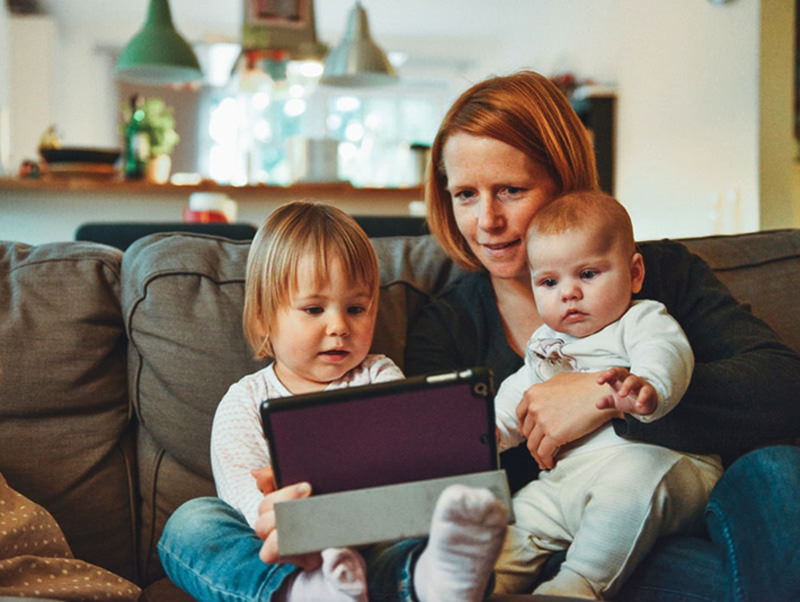mamma figli piccoli tablet divano casa bebè