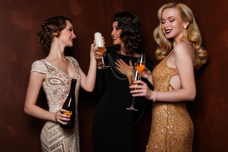 7 consigli di bellezza per essere belle per le Feste di Natale brindisi donna capelli lunghi biondi abito oro capelli castani abito nero look vintage anni 20 calici spumante