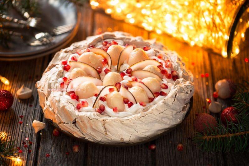 torta pavlova di natale meringa panna montata melograno fette pere luci albero