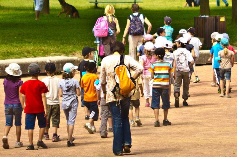 Gite scolastiche per bambini: quali sono le mete migliori? prato parco case ragazzi zaini insegnante maestra donna capelli biondi cappellini