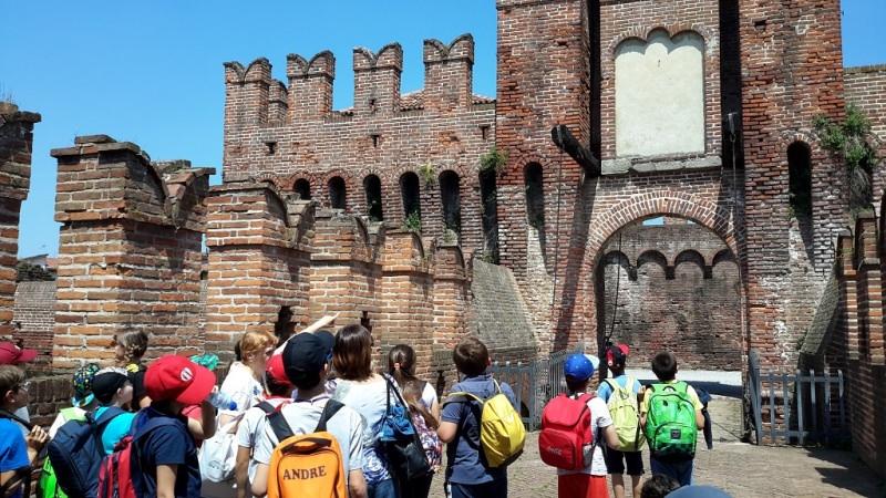 Gite scolastiche per bambini: quali sono le mete migliori? ingresso rocca sforzesca borgo antico Soncino Cremona gita ragazzi zaini berretti