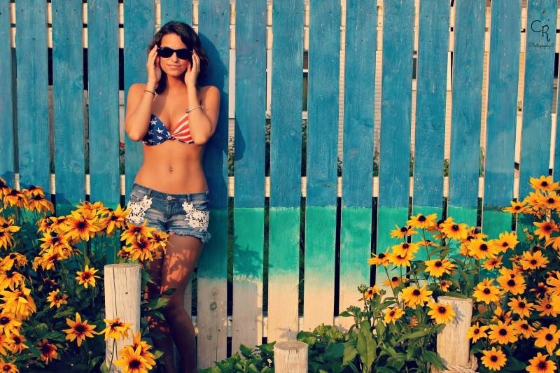 3 trattamenti estetici per arrivare pronte all'estate bellezza corpo donna capelli castani occhiali da sole reggiseno stampa bandiera americana strisce rosso bianche blu stelle bianche shorts jeans fiori gialli cancello legno azzurro