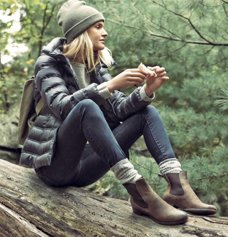 L'abbigliamento tecnico femminile per il trekking donna capelli lisci biondi berretto lana grigio jeans tronco legno albero natura