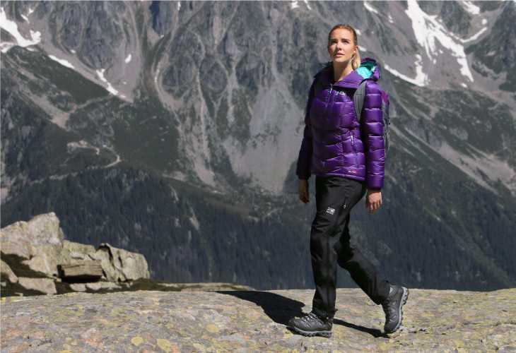 L'abbigliamento tecnico femminile per il trekking donna passeggiata montagna scarponi pantalone legno giubbotto impermeabile viola zaino capelli biondi montagna neve
