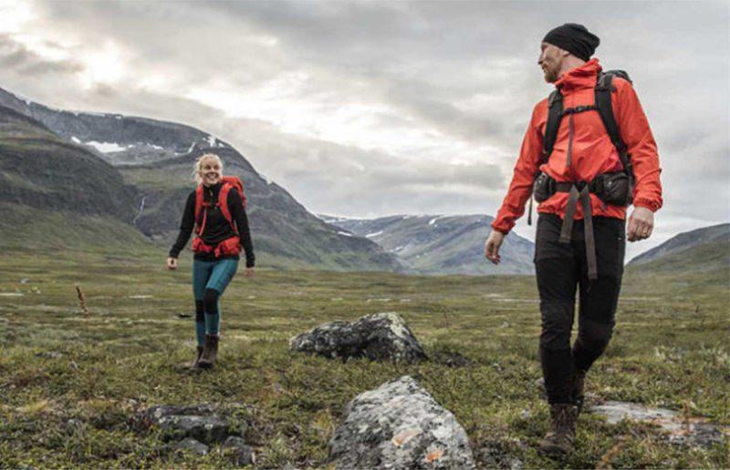 L'abbigliamento tecnico femminile per il trekking natura donna sorridente capelli biondi jeans scarponi erba uomo giacca rossa zaino montagne