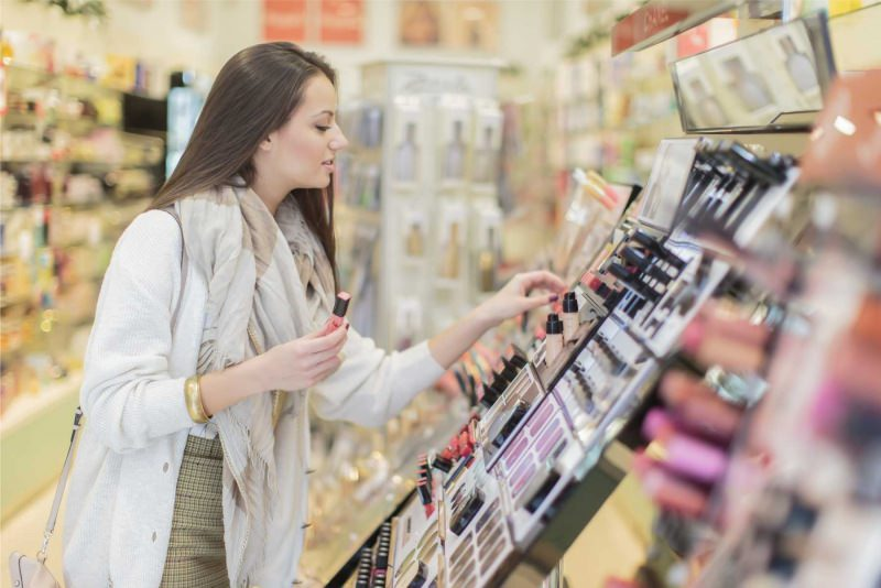 Cosmetici, conviene di più comprare online? Perché scegliere di acquistare in e-commerce? espositore prodotti negozio fisico trucco make up donna capelli lisci castani sciarpa beige giacca cardigan bracciale oro borsa smalto rosa