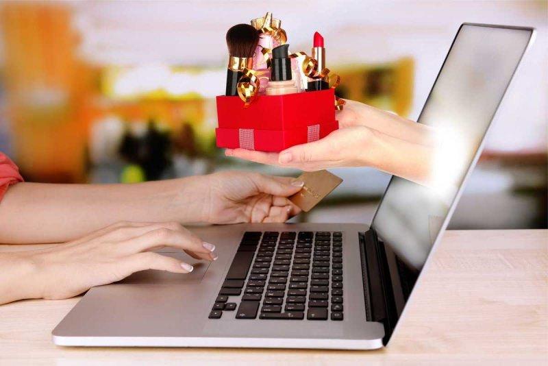 Cosmetici, conviene di più comprare online? Perché scegliere di acquistare in e-commerce? laptop notebook tastiera mani donna french manicure carta di credito pacco regalo rosso makeup rossetto fondotinta pennello nastro oro dorato