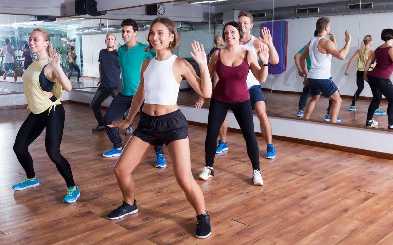 uomini e donna ballano insieme zumba palestra fitness