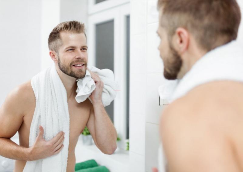 giovane uomo bello attraente barba sorriso allo specchio telo spugna routine mattino