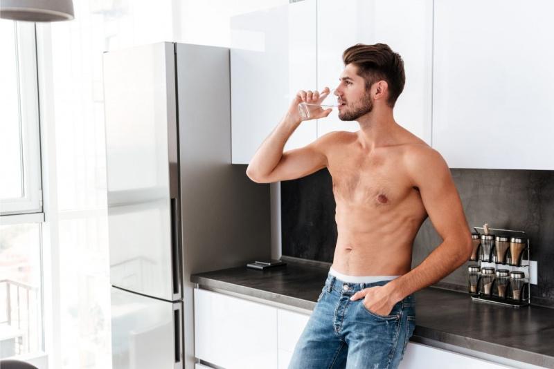 uomo bello e attraente beve un bicchiere d'acqua in cucina jeans dorso nudo