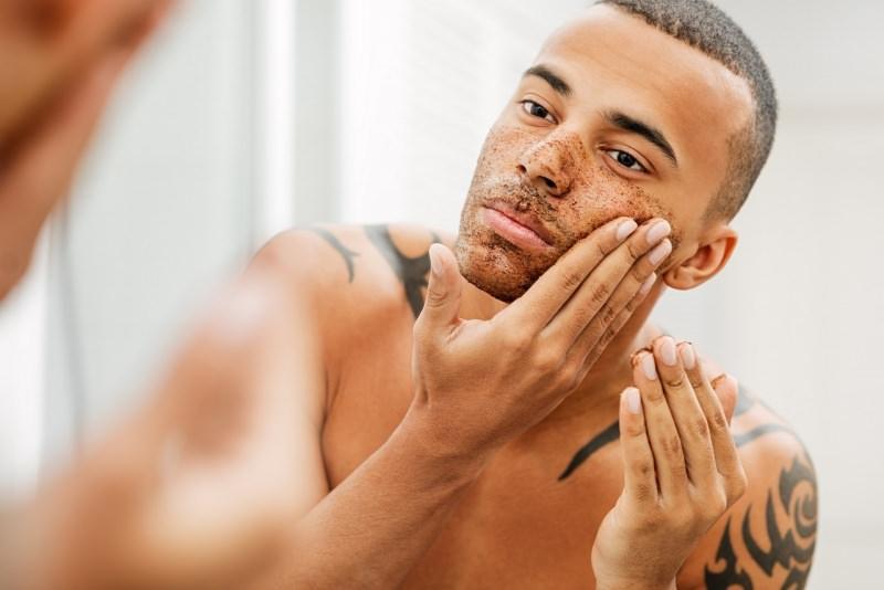 uomo bello applica scrub caffe su viso allo specchio bagno
