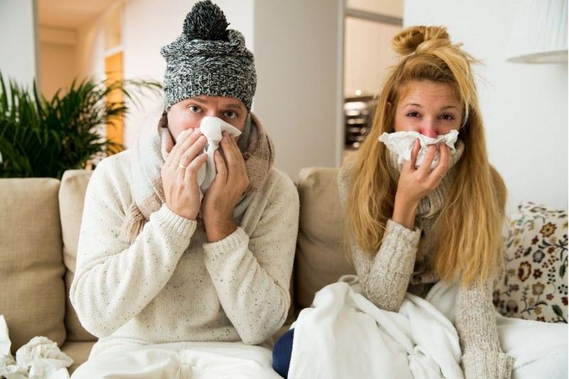 raffreddore uomo cappello donna soffiano naso fazzoletto carta divano casa