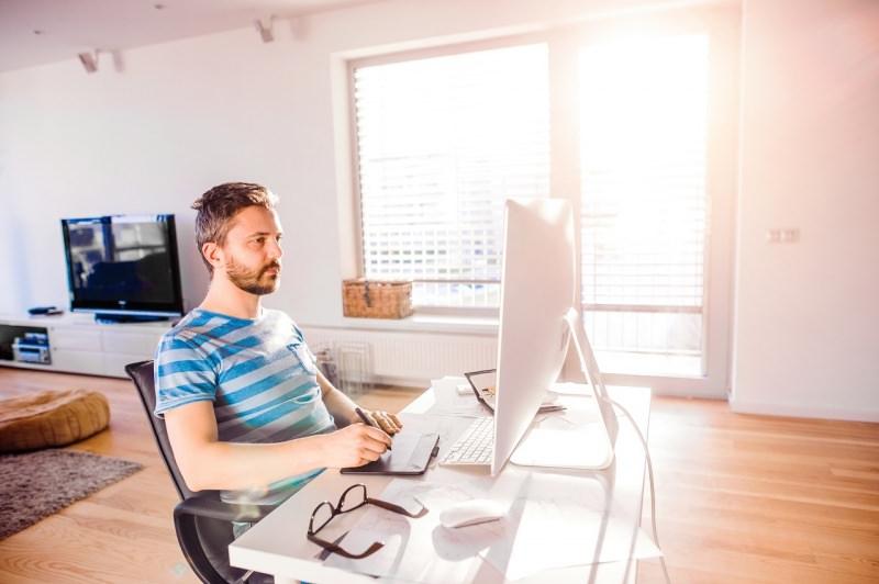 uomo alla scrivania lavoro da casa soggiorno smart working computer monitor luce finestra