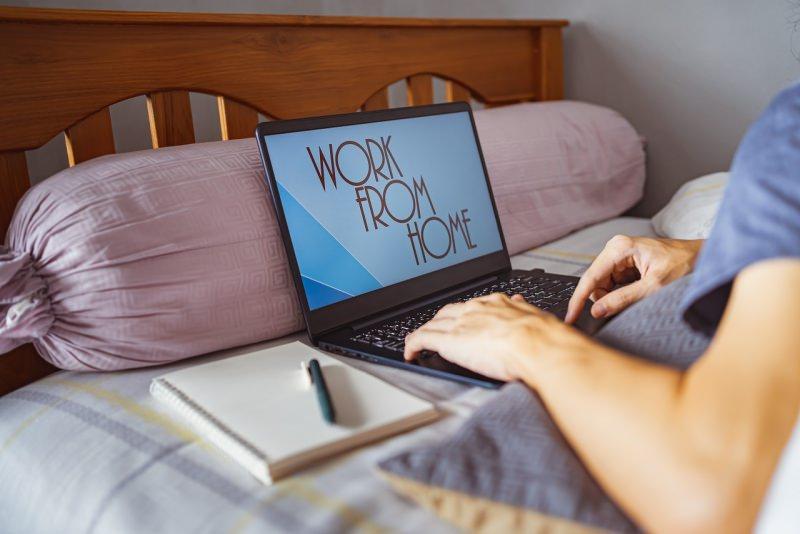 smart working lavoro da casa laptop letto uomo