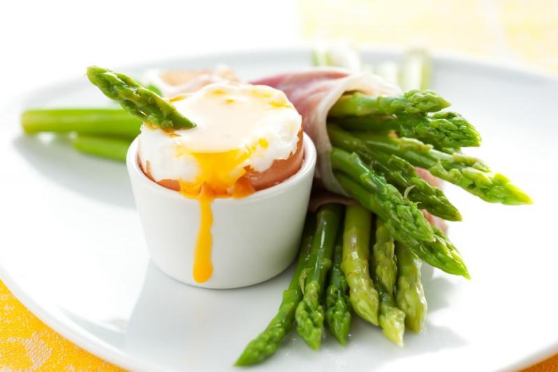 Uova con asparagi avvolti nel prosciutto antipasto uovo alla coque porta uovo piatto pronto colazione tovaglia gialla