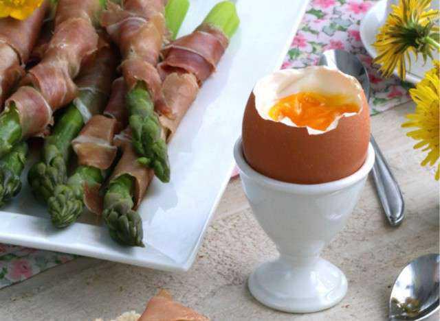 Uova con asparagi avvolti nel prosciutto porta uovo alla coque piatto pronto antipasto colazione fiori gialli cucchiaino