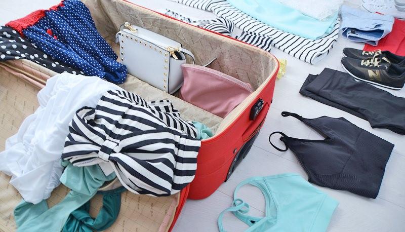 La spiaggia ti aspetta! Ecco tutto ciò di cui hai bisogno la prossima estate cosa mettere in valigia preparare bagagli trolley rosso abiti borsa bianca vestito righe bianco nero scarpe