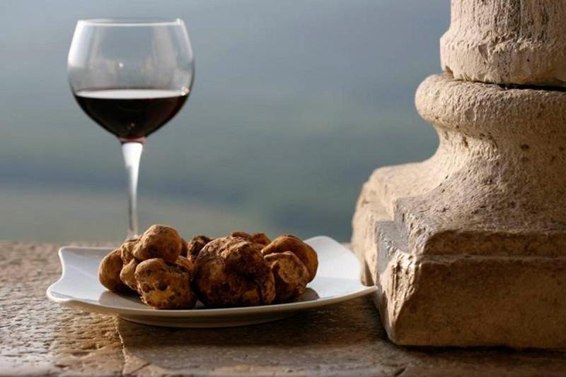 I migliori abbinamenti tra vino e tartufo bicchiere calice cristallo vino rosso piatto quadrato tartufi bianchi muro colonna pietra panorama