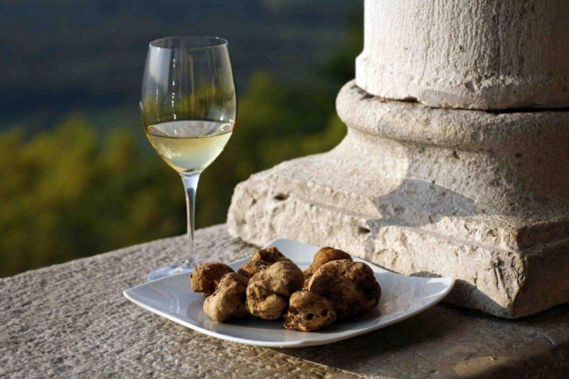 I migliori abbinamenti tra vino e tartufo calice cristallo vino bianco piatto quadrato tartufi neri muro molonna pietra panorama natura