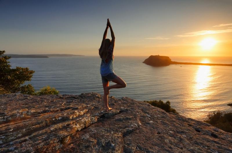 donna fa yoga davanti al mare al sorgere del sole